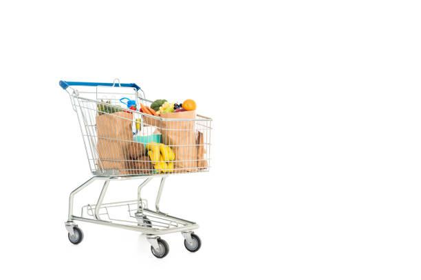 papiertüten voller obst und gemüse in den einkaufswagen - trolley kaufen stock-fotos und bilder