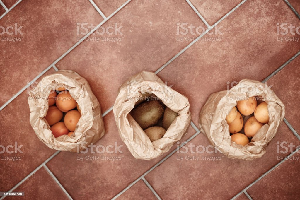 paper bags of apricots, kiwis, loquats royalty-free stock photo