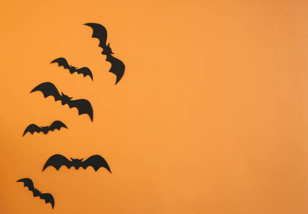 Paper bats flying on orange background. Halloween decoration concept stock photo