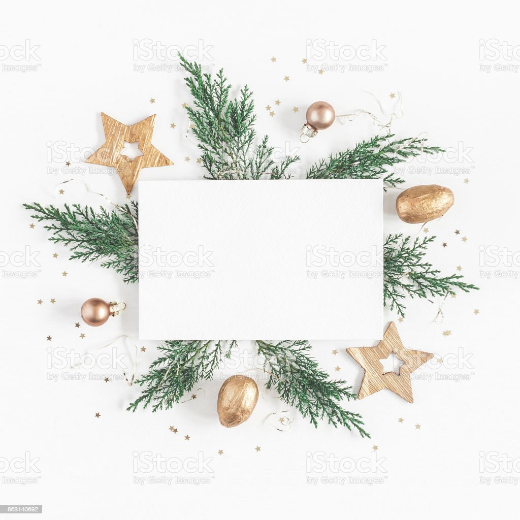 Paper blank, christmas tree branches, golden decorations. Flat lay stock photo