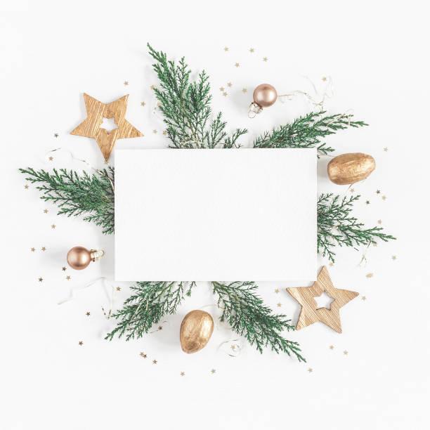 Papel en blanco, ramas de árbol de Navidad, adornos de oro. Endecha plana - foto de stock
