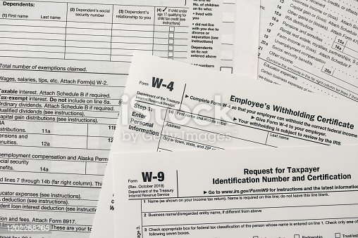 184625018 istock photo Paper blanks of 1040, w4 and w9 tax form close up 1202288265