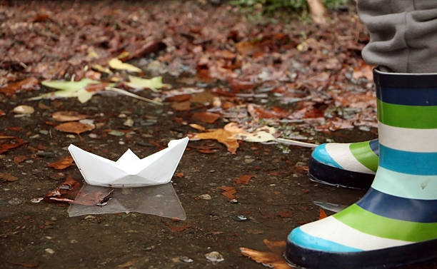 Paper boat in puddle next to child in rubber boots – Foto