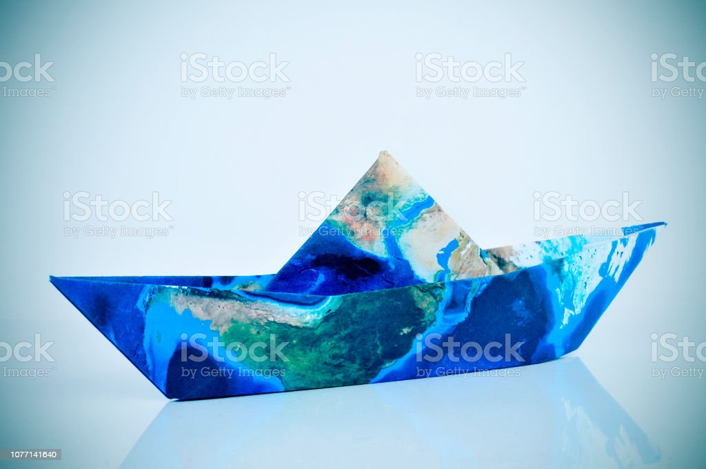 a paper boat made with a world map , with a slight vignette added