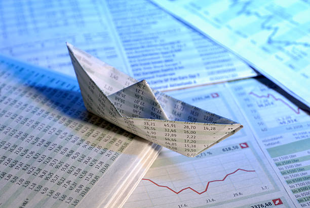 A paper boat on a sea of graphs and paperwork stock photo