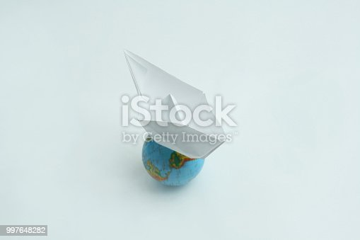 istock paper boat on the globe.isolated on a white background 997648282