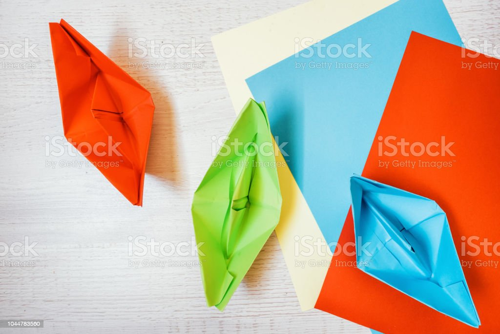 colorful paper boats, paper ships and colorful papers on wooden desk