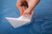 Hand with a paper boat on blue water