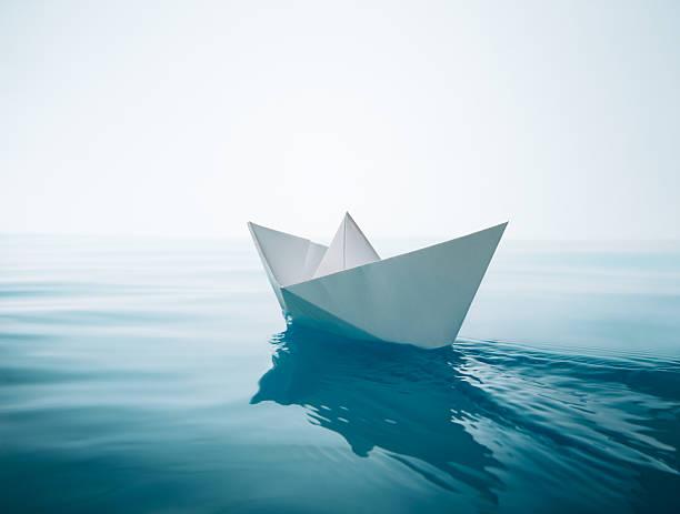 paper boat sailing stock photo