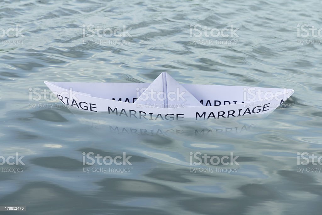 Close-up of a sinking paper boat with the text \'Marriage\'.