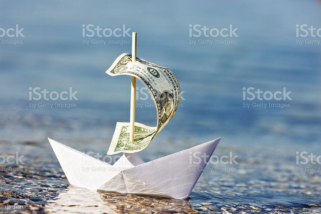 Paper boat with $1 bill sail is blown onshore stock photo