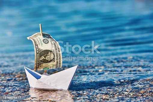 Plenty of financial concepts in this image of a paper boat with a one-dollar banknote as a sail, with copy space in the water.