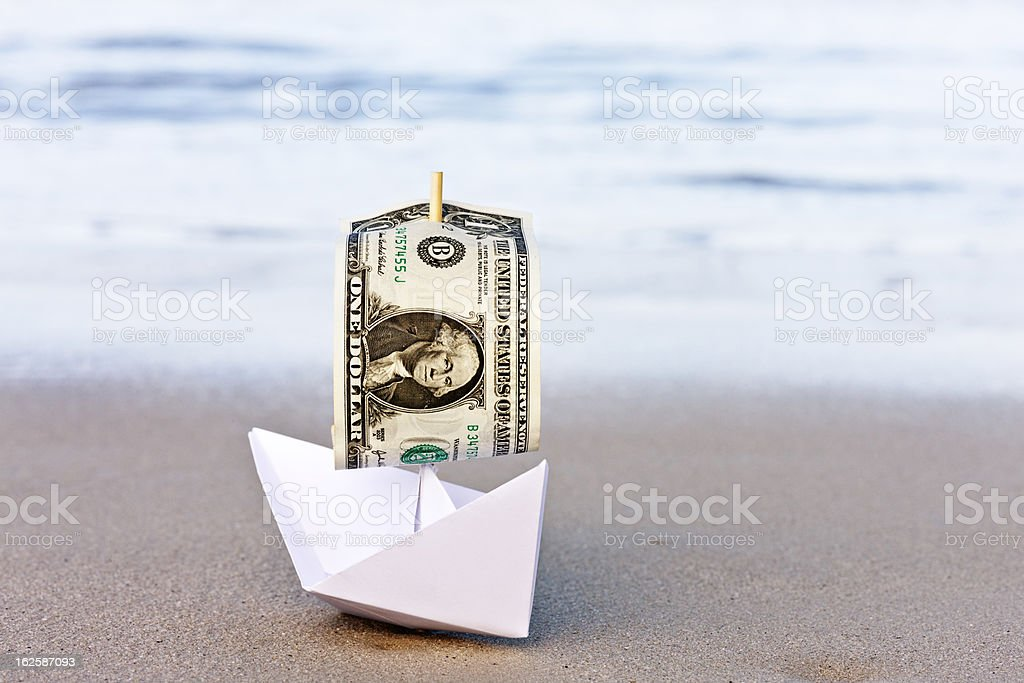 Paper boat with $1 sail runs aground and is stranded stock photo