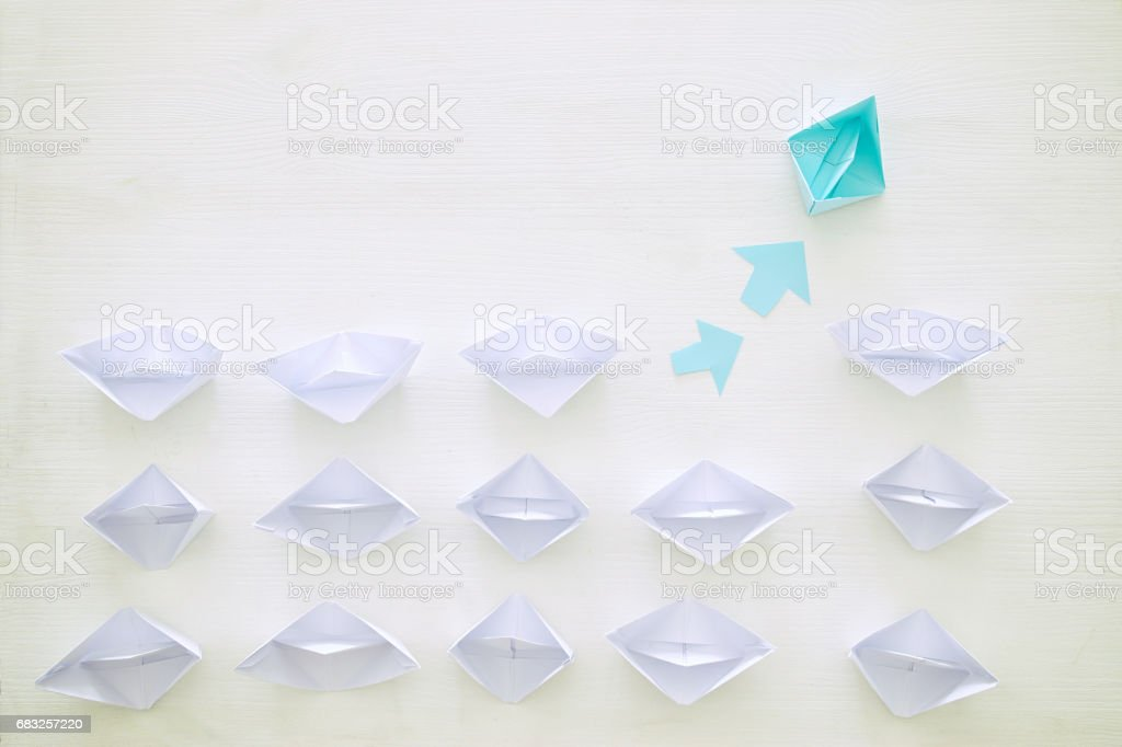 top view image of paper boats over wooden background and one...