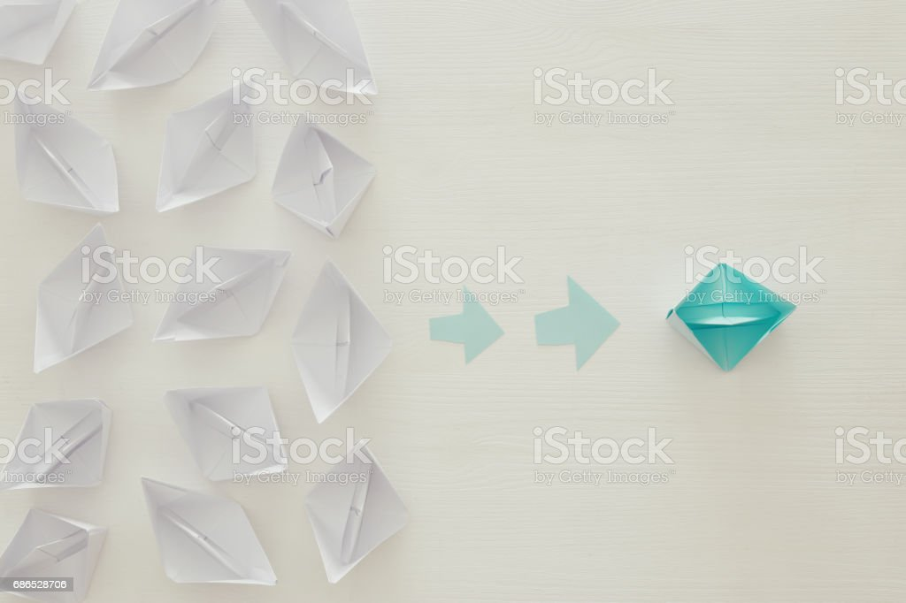paper boats and one individual boat choosing different path zbiór zdjęć royalty-free
