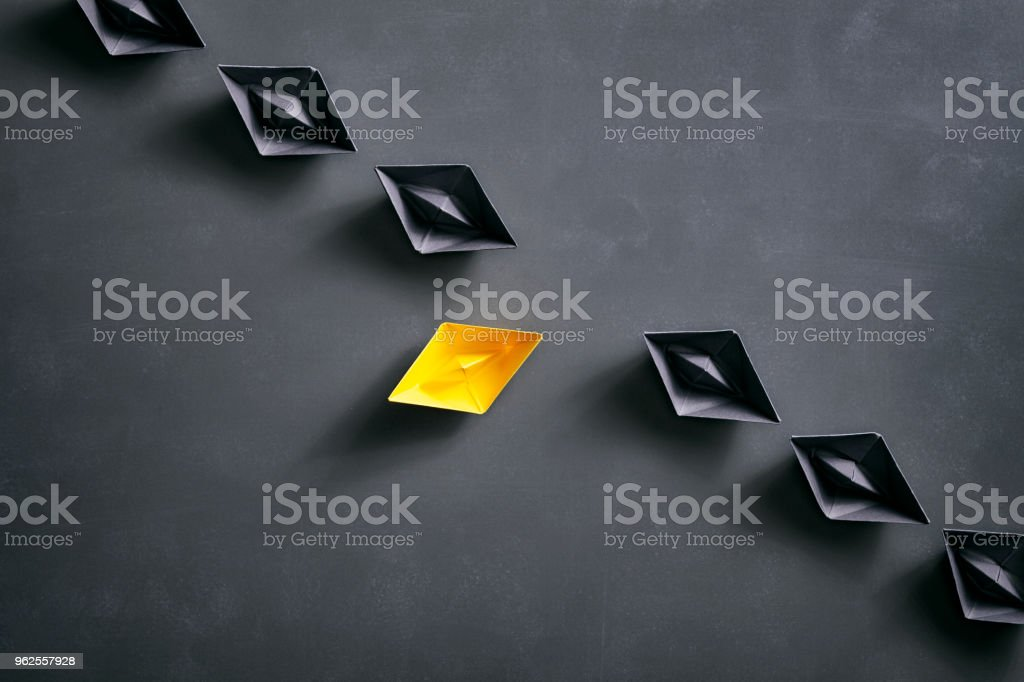 Conceptual photography with black and yellow paper boats on a smudged...