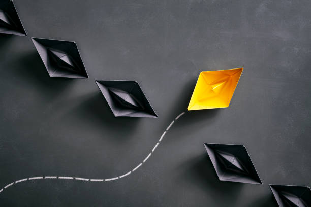 Paper boats on blackboard - Origami Yellow Concept stock photo