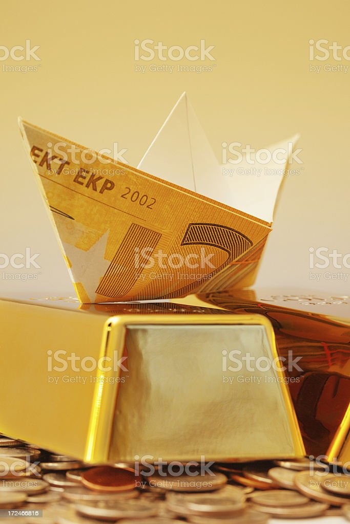 Paper boats on gold ingot royalty-free stock photo