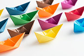 Multi coloured paper boats on white background.