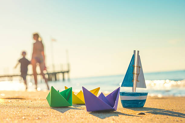 paper boats, wood boat and walking people at the beach – Foto