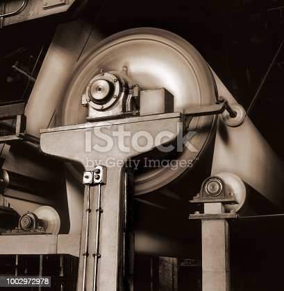 Black and white image with sepia toning of rolling drums in a paper factory machine.