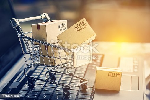 istock Paper boxes in a shopping cart on a laptop keyboard. Ideas about e-commerce, e-commerce or electronic commerce is a transaction of buying or selling goods or services online over the internet. 870527480