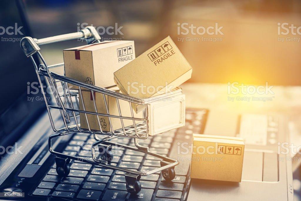 紙は、ノート パソコンのキーボードのショッピング カートのボックスします。E-コマース、電子商取引や電子商取引についてのアイデアは、買うか、またはインターネット上の商品やサービスをオンラインで販売するトランザクションです。 ストックフォト