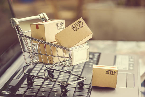 Paper boxes in a shopping cart. Paper boxes in a shopping cart on a laptop keyboard. Ideas about e-commerce, e-commerce or electronic commerce is a transaction of buying or selling goods or services online over the internet. sea channel stock pictures, royalty-free photos & images