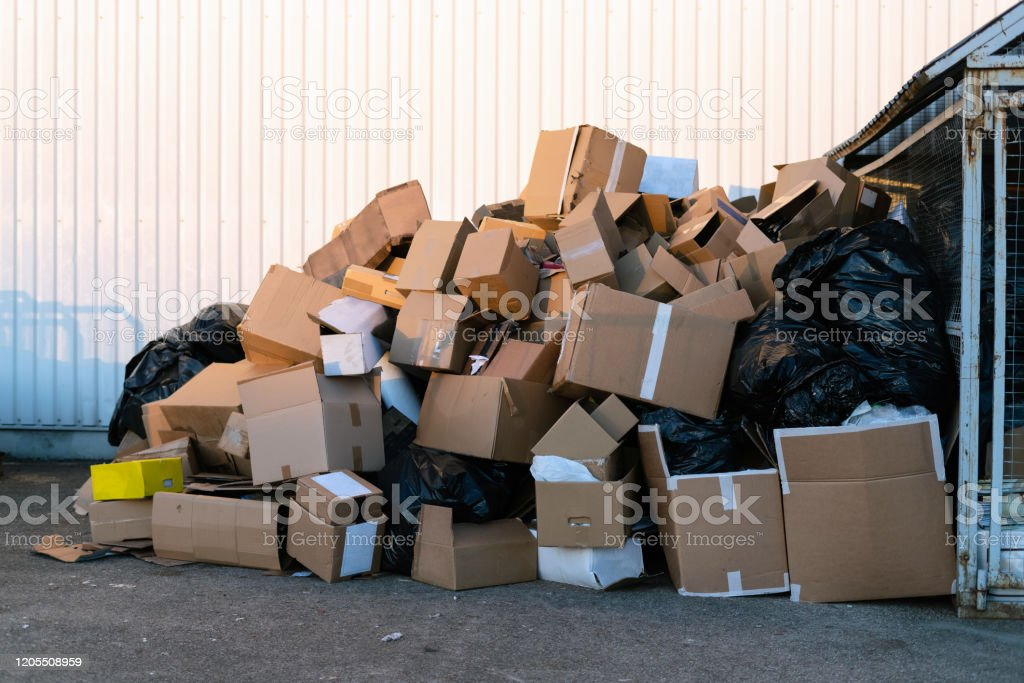 Paper boxes next to a garbage bin. Stack of paper waste outdoor in...