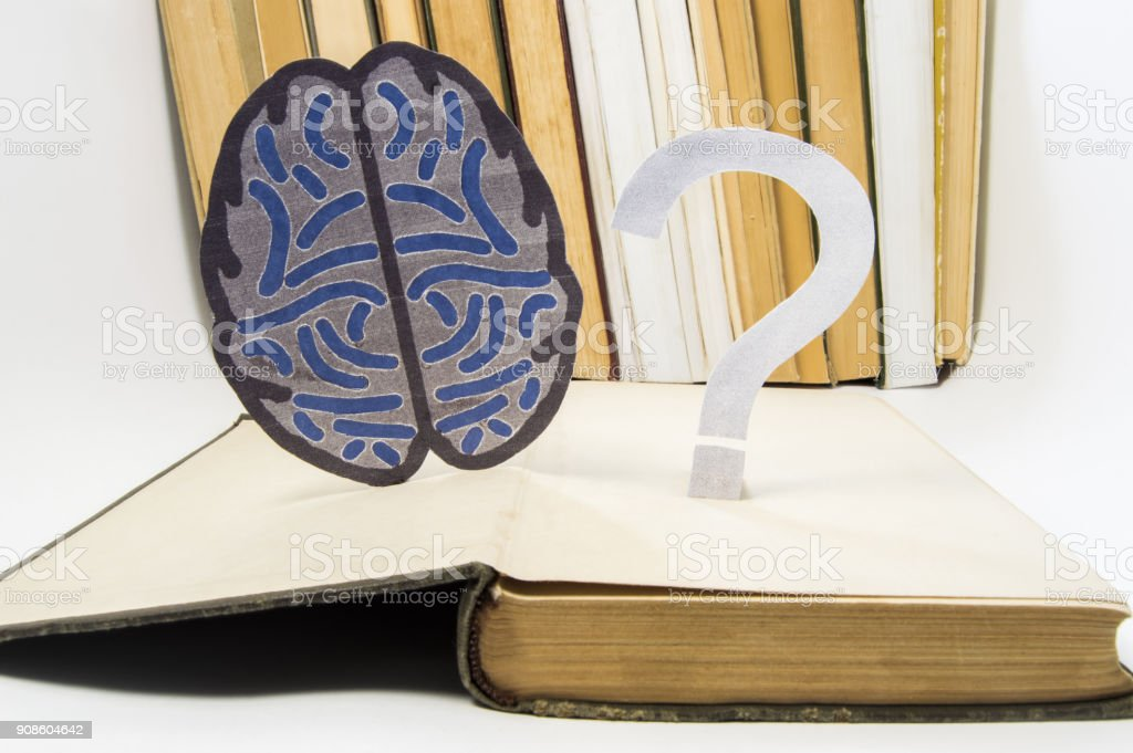 Paper brain silhouette and question mark is over old open medical book. Photo to refer issues and questions in study of brain, as well as difficulties in diagnosis in neurology and neuroscience stock photo