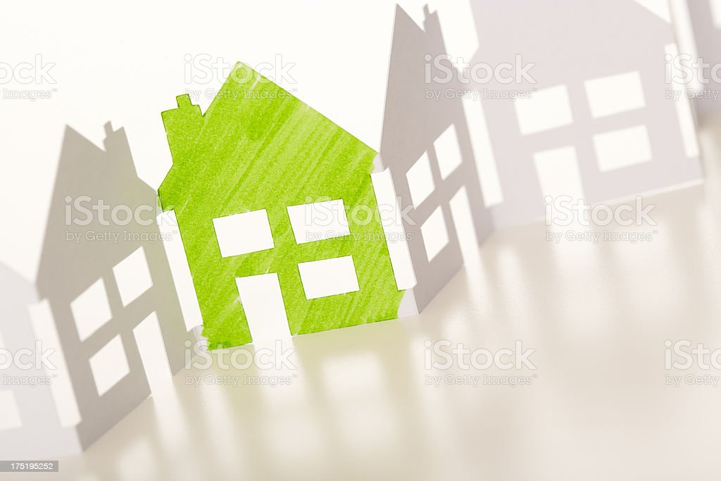 Paper chain houses one coloured green stock photo