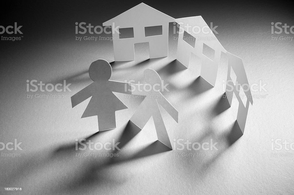 Paper chain people and house symbol in spotlight royalty-free stock photo