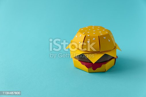 1134487598 istock photo Paper cheeseburger with beef, cheese and sauce on a blue background. Copy space. Creative or art food concept 1134487600