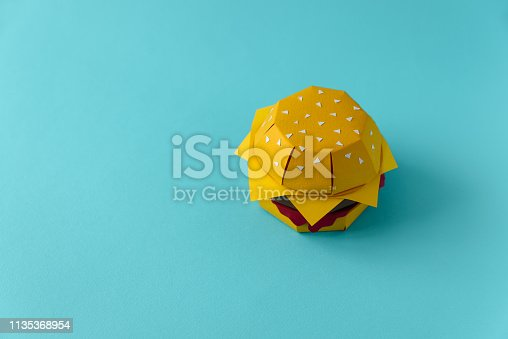 istock Paper cheeseburger with beef, cheese and sauce on a blue background. Copy space. Creative or art food concept 1135368954