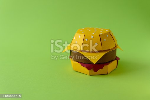 1134487598 istock photo Paper cheeseburger with beef, cheese and sauce on a green background. Copy space. Creative or art food concept 1134487715