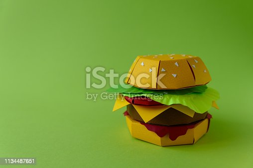 1134487598 istock photo Paper cheeseburger with beef, cheese, tomato, lettuce and sauce on a green background. Copy space. Creative or art food concept 1134487651