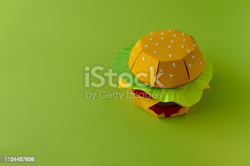 1134487598 istock photo Paper cheeseburger with beef, cheese, tomato, lettuce and sauce on a green background. Copy space. Creative or art food concept 1134487656