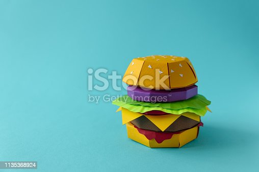 istock Paper cheeseburger with beef, cheese, tomato, lettuce, onion and sauce on a blue background. Copy space. Creative or art food concept 1135368924