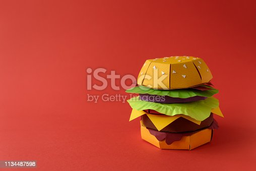 istock Paper cheeseburger with beef, cheese, tomato, lettuce, onion, bacon and sauce on red background. Copy space. Creative or art food concept 1134487598