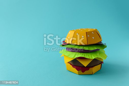 1134487598 istock photo Paper cheeseburger with beef, cheese, tomato, lettuce, onion, bacon and sauce on a blue background. Copy space. Creative or art food concept 1134487624