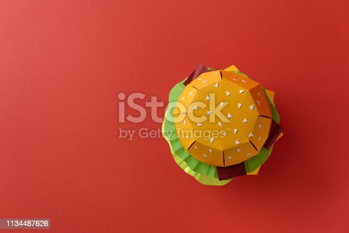 1134487598 istock photo Paper cheeseburger with beef, cheese, tomato, lettuce, onion, bacon and sauce on red background. Copy space. Creative or art food concept 1134487626