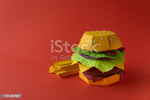 1134487598 istock photo Paper cheeseburger with beef, cheese, tomato, lettuce, onion, bacon and fries on red background. Copy space. Creative or art food concept 1134487637