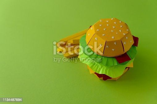 1134487598 istock photo Paper cheeseburger with beef, cheese, tomato, lettuce, onion, bacon and fries on green background. Copy space. Creative or art food concept 1134487694