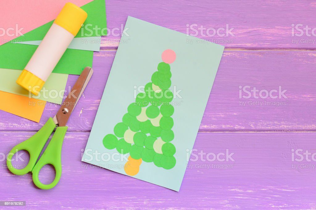Paper Christmas greeting card, colored paper sheets set, scissors, glue stick on a wooden table. Easy Christmas crafts for children to make. Children imagination and creativity. Top view stock photo