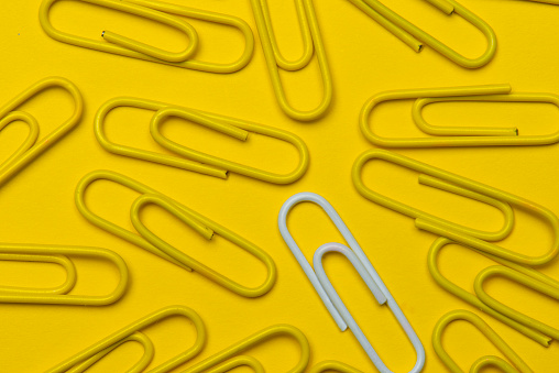 Yellow and gray paper clips over yellow background.