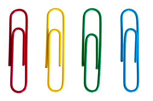 Selection of multi-colored paper clips on isolated white background.