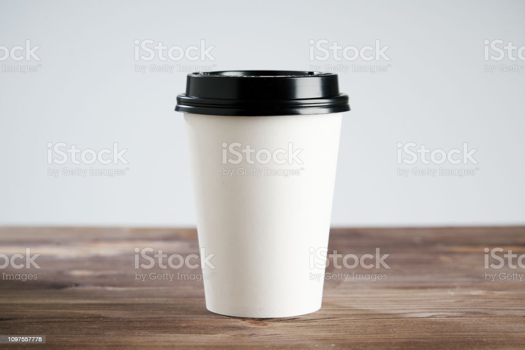 Paper coffee cup disposable for take away or to go, at wooden table,...