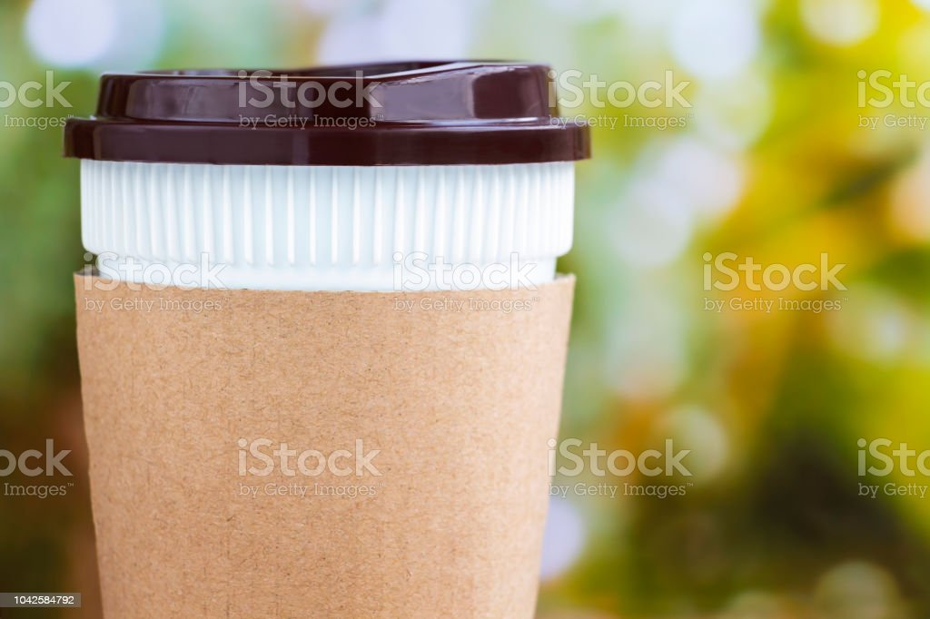 Paper coffee cup or disposable cup on the natural morning background...