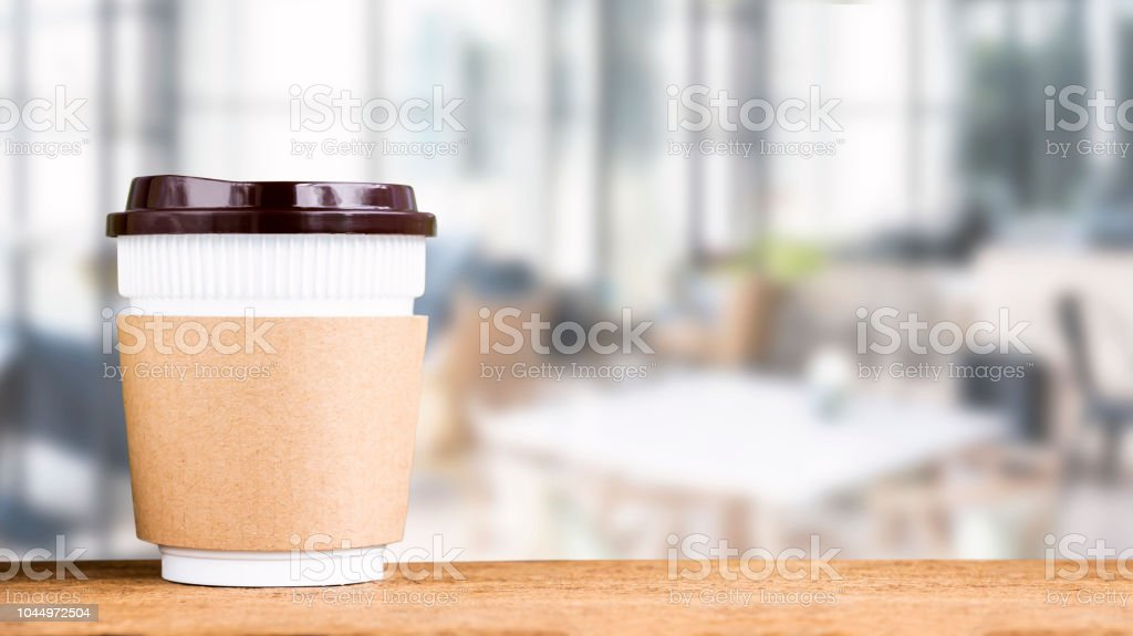 Paper coffee cup or disposable cup on the wooden table on café coffee...