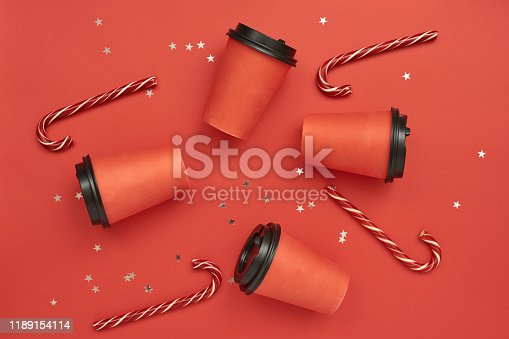 Paper coffee cup with sugar canes on a red background. Christmas background with Xmas candy canes and star confetti. Top view, flat lay, mockup. Copy space for text.